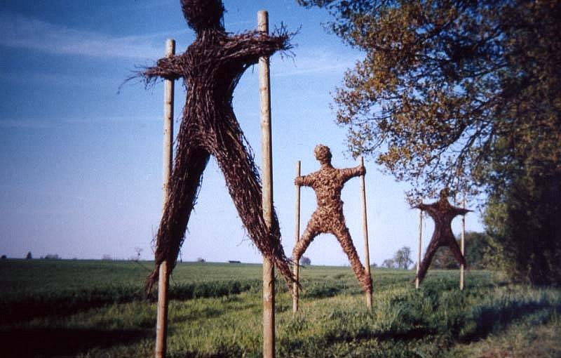 Strijdom van der Merwe, Three Men Walking on Stilts 2005, installation sculpture made from material found in wood