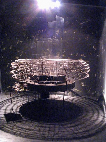 Mark Esper, Second Orrery 2005, welded steel, n-gauge train tracks, steel pan, water bucket with pump, electric cooktop, acrylic vanes in wooden bases, electronic circuitry, overhead lamp, gold leaf n-gauge train