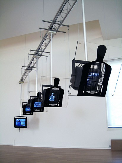 Dara Birnbaum, Hostage 1994/2010, Installation - 6 channel color video with 6 channels of stereo audio; 4 plexiglass target/shields; inter-active last component
