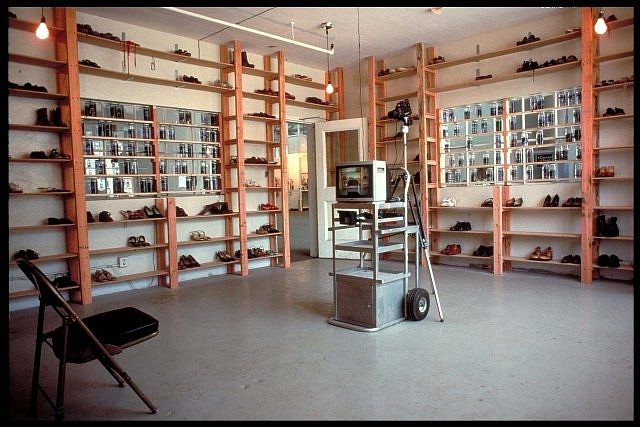Seyed Alavi, Departure Room 1989, shoes, shelves, photo transparency, water, video monitor, camera, chair, motion detector, lights